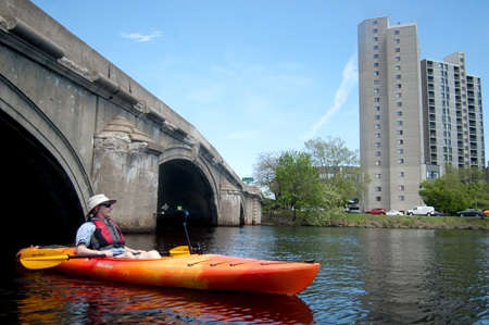 Photographer Richard Hackel passes under the Cambridge Street bridge along the Charles River.