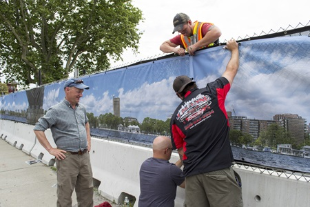 Richard Hackel watches his photo-mural being installed around the King Open and Cambridge Street Upper Schools and Community Complex, June 27, 2017.