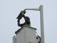 Worker installing a light fixture