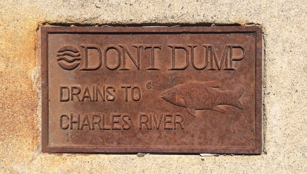 Sign on sidewalk saying don't dump - drains to charles