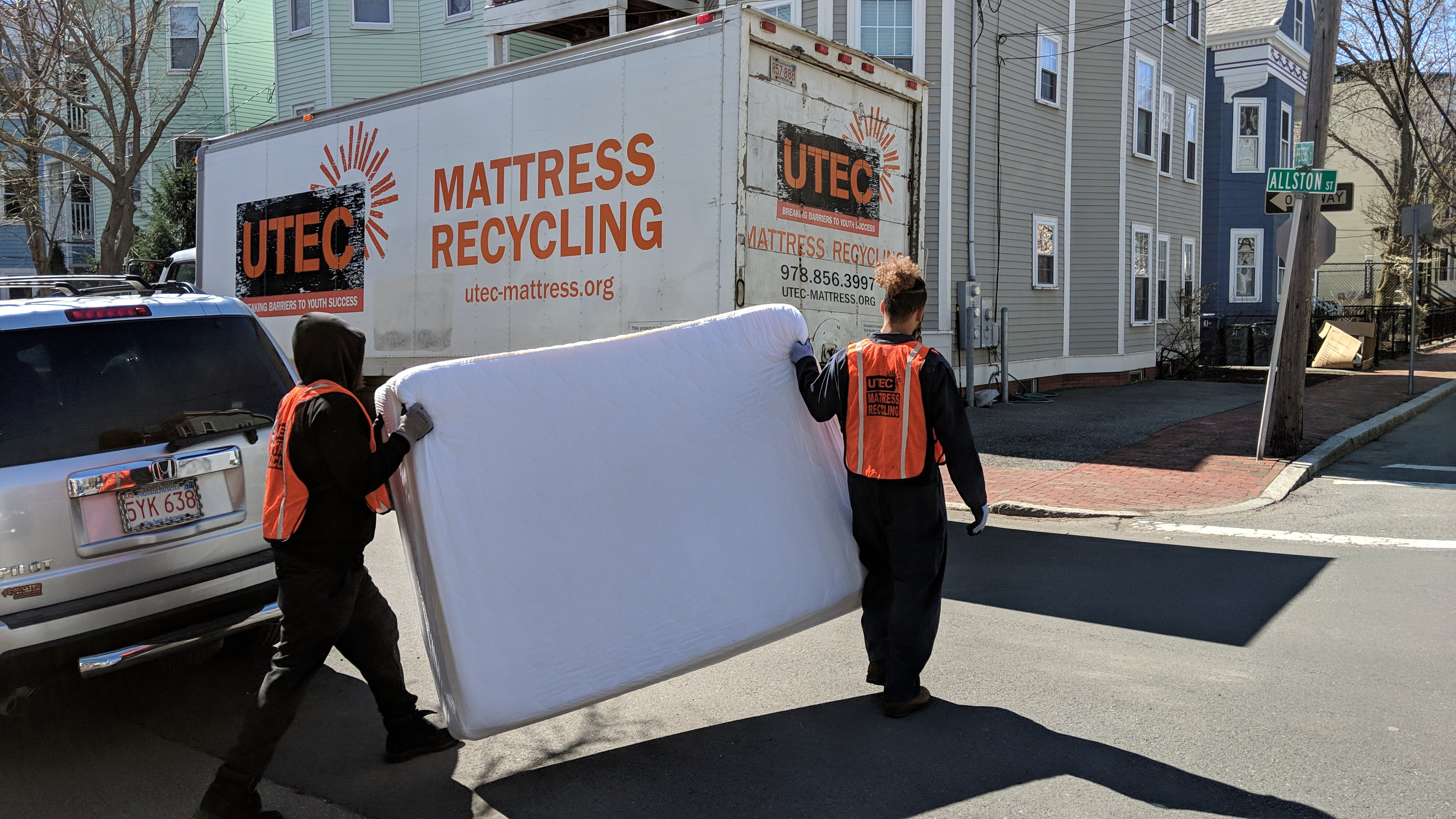 Two people carrying a mattress to a truck