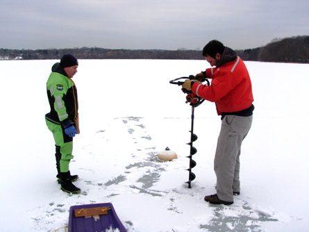 CWD staff starts to drill a hole through the ice while Fire Department staff watches for safety.