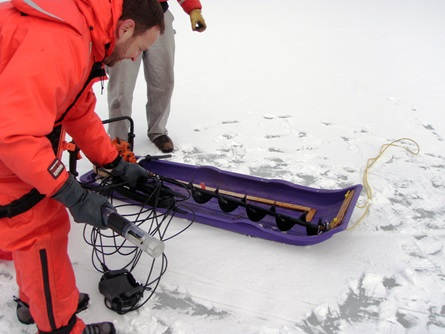 Preparing the multiprobe for measuring temperature and dissolved oxygen levels in the water beneath the ice.