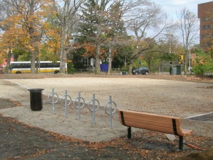 Bikerack and bench placed at the soccer field.